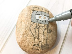 After you outline your design, start by painting in the mask on your Star-Lord rock
