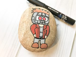 Use a thin black pen to outline Star-Lord on your rock
